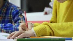 Bild von 2 Kindern, die an einem Tisch sitzen. Das vordere Kind malt mit einem roten Buntstift in ein Heft. Neben dem Heft liegen weitere Buntstifte in verschiedenen Farben.