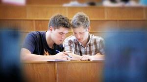 Bild eines Hörsaals. Im Mittelpunkt sind 2 männliche Studenten, die nebeneinander sitzen und gemeinsam in die Unterlagen schauen. Im Hintergrund sind weitere Studierende zu erkennen.