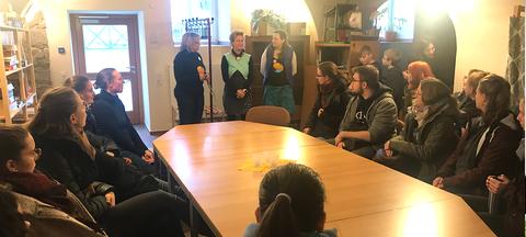Bild einer Gruppe von Menschen, die in der Schkola Grund- und Oberschule Ostritz um eine Tafel sitzen und 3 Frauen zuhören, die im Hintergrund stehen.