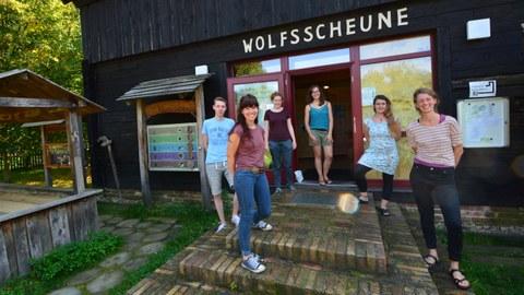 """Foto: 6 Personen in Sommerkleidung stehen vor dem Eingang zu einem hölzernen Gebäude. Über der Eingangstür ist die Aufschrift """"Wolfsscheune"""" angebracht."""