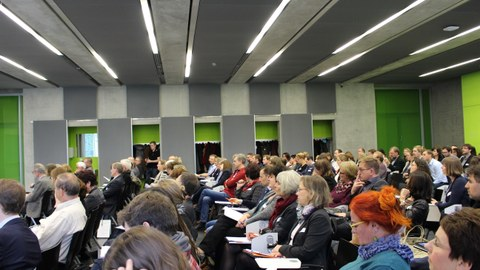 Bild eines vollbesetzten Hörsaales an der Fakultät Informatik der TU Dresden. Die Sitzenden hören augenscheinlich einen Vortrag. Einige machen sich nebenbei Notizen.