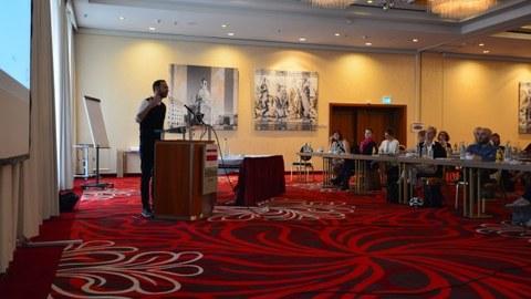 Foto: In einem Konferenzsaal steht ein Redner am Pult