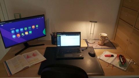 Foto: Schreibtisch mit Bildschirm, Laptop, Lampe und anderen Gegenständen