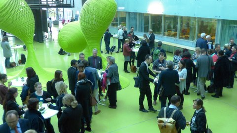 Bild vom Foyer des Gebäudes der Fakultät Informatik der TU Dresden. Menschen stehen in Kleingruppen um Stehtische und reden miteinander.