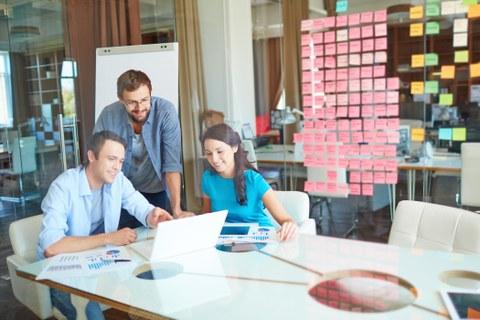 Das Foto zeigt drei Personen in einem Büro. Sie schauen gemeinsam in einen Laptop und reden miteinander. An den Wänden kleben viele Notizzettel.