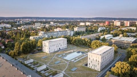 Das Foto zeigt eine Luftaufnahme der Gebäude der Sächsischen Landes- und Universitätsbibliothek. Zwischen den beiden Hauptgebäuden befindet sich eine große Grünfläche. Diese ist von einem Netz aus kleinen Wegen durchzogen.