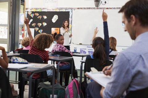 Das Foto zeigt eine Referendarin beim Unterrichten einer Grundschulklasse. Viele Lernende melden sich. Im Vordergrund sitzt der Lehrer und macht sich Notizen auf einem Klemmbrett.