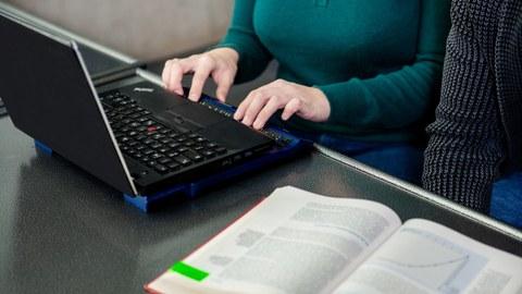 Foto: Eine Frau schreibt an einem Laptop mit Braille-Zeile. Ein Buch liegt auf dem Tisch.