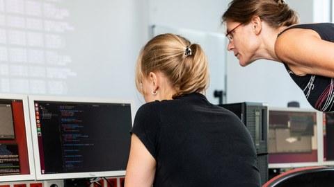Foto: Eine Studentin und eine Dozentin beugen sich über einen Monitor in einem Computerkabinett.