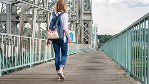 Eine Studentin hält Lernmaterial in der Hand und läuft über das Blaue Wunder.