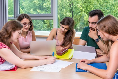 Foto von fünf Studenten, die in einer Workshoprunde zusammen am Laptop lernen.