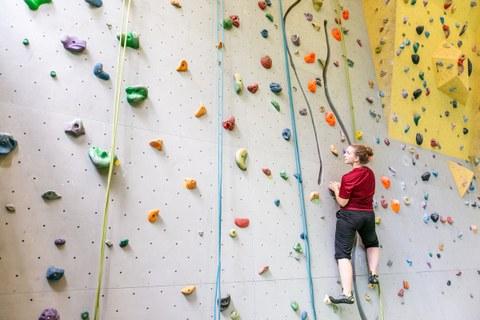 Foto einer Frau, die an einer Kletterwand klettert