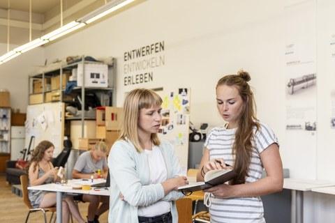 Foto: Vier Frauen in einer Bastelwerkstatt. Die einen basteln und die anderen schauen in ein Buch.