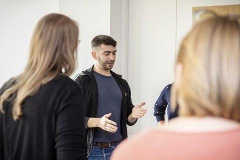 Foto eines Mannes, der gestikulierend in einer Gruppe von Personen steht, die ihm zugewandt sind.