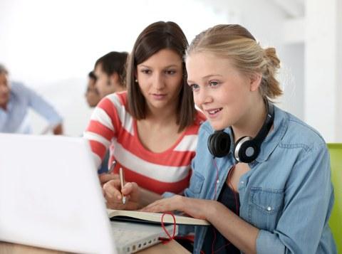 Das Foto zeigt zwei Studentinnen, die gemeinsam auf einen Laptop schauen und sich etwas in ein Heft notieren.