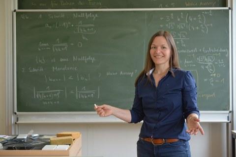 Foto: eine junge Frau steht vor einer Tafel, an die mit Kreide mathematische Formaln geschrieben sind.
