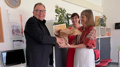 Foto: drei Personen stehen in einem Raum. Einer Person wird ein Geschenk übergeben.