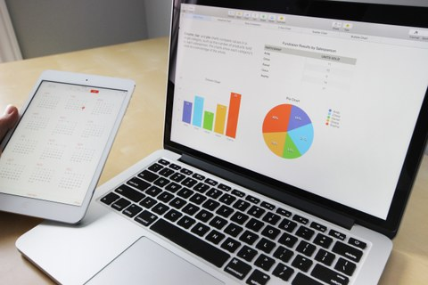 Bild eines Laptops, der offen auf einem Tisch steht. Eine Tabelle und zwei Diagramme sind auf dem Bildschirm zu erkennen. Im linken Teil des Bildes hält eine Hand ein Tablet, auf dem ein Kalender geöffnet ist.