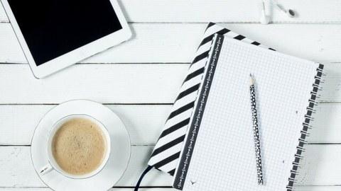 Foto: Auf einem Tisch liegt ein Tablet, ein Notizblock und steht eine Tasse Kaffee