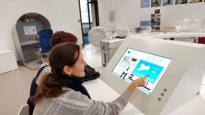 Eine weibliche Person zeigt etwas auf einem Display/Lernprogramm im Dresdner Verkehrsmuseum. Neben ihr sitzt eine zweite Person, die ebenfalls auf das Display sieht. Im Hintergrund sieht man den Museums-Ausstellungsraum.