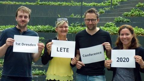 """Foto von vier Personen, die jeweils ein Blatt Papier vor sich halten. Die aufschrift der vier Blätter ergibt zusammen den Text """"1st Dresden LETE Conference 2020"""""""