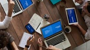 Auf dem Bild wird ein Tisch aus der Vogelperspektive gezeigt, an dem mehrere Personen mit ihren Laptops arbeiten