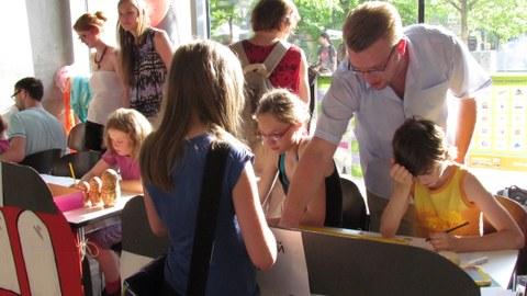 Bild mit mehreren Personen, darunter ein Großteil Kinder, die teilweise an einem Tisch sitzen, teilweise daneben stehen und malen, zeichnen oder zuschauen.