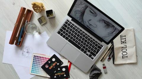 Auf dem Bild sehen Sie einen kreativen Arbeitsplatz mit einem Laptop in der Mitte