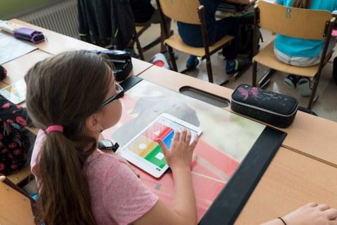 Mädchen sitzt an ihrem Platz im Klassenraum. Auf ihrem Tisch liegt ein Tablet.