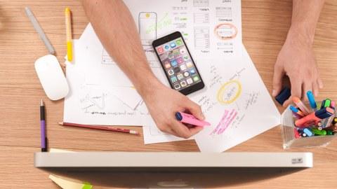Foto eines Schreibtisches mit Blick von oben auf verschiedene Blätter und Stifte