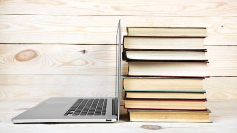 Foto eines Laptops und einem Bücherstapel